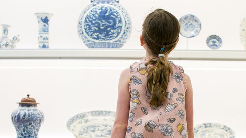 young girl looking at ceramics