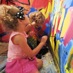 young girls painting on a wall