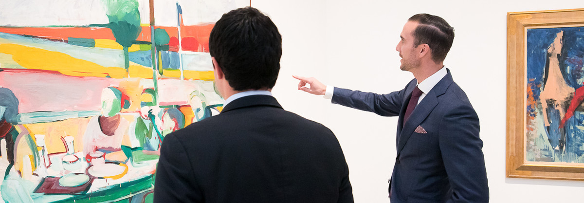 Two men looking at paintings in a gallery