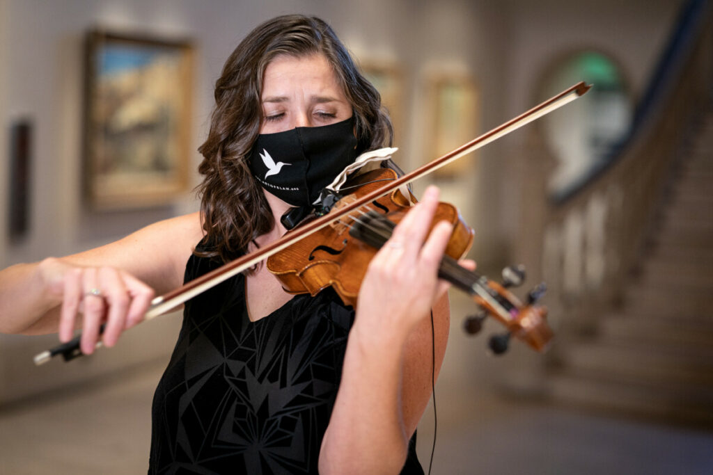 Art of Elan - Picture of Kate Hatmaker, Art of Elan Executive and Artistic Director, performing on violin in The San Diego Museum of Art rotunda. Photo by Gary Payne. Courtesy of Art of Elan.